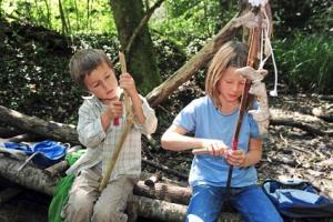 Kinder schnitzen im Wald